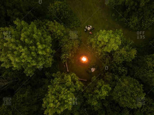Aerial view of friend eating close to campfire in forest at night