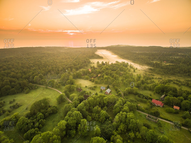 Aerial view of houses in foggy forest in countryside of Estonia at sunset
