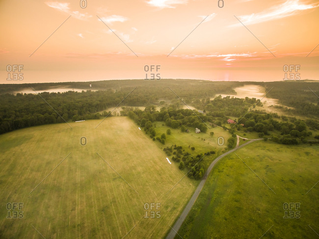 Aerial view of foggy meadow in countryside at sunset in Estonia