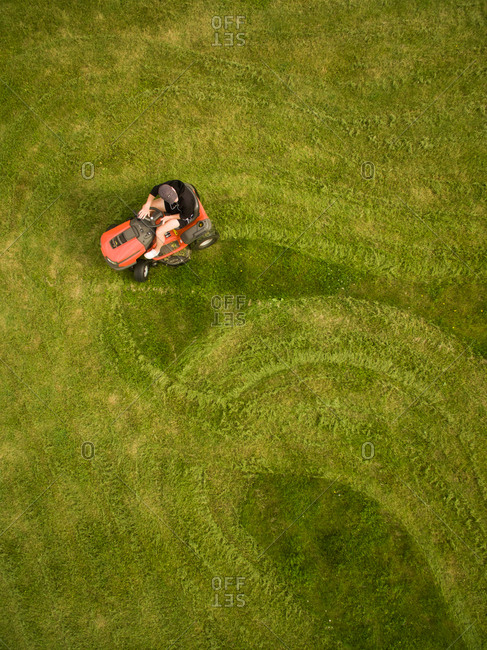 Aerial view of a man mowing the lawn creating shapes