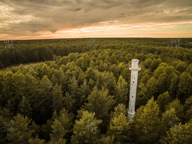 Aerial view of a lighthouse in the middle of forest with a stormy sky in Estonia