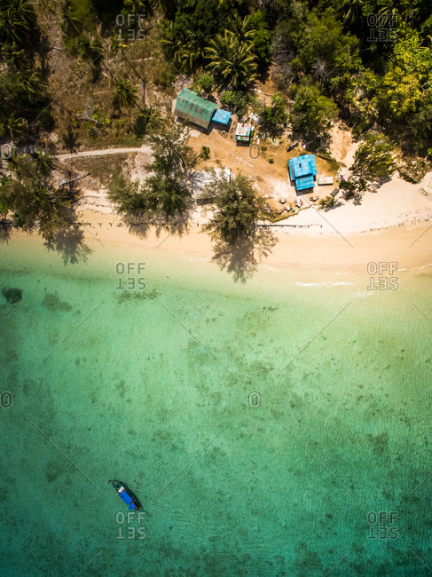 Aerial view of a boat moored in the paradisiacal sea close to small houses on the beach in Chao Mai National Park in Thailand