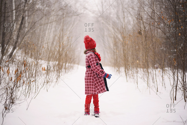 Full length view of young girl turning away as snow falls