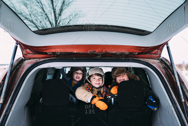 Kids smiling as they look out of hatch back of car
