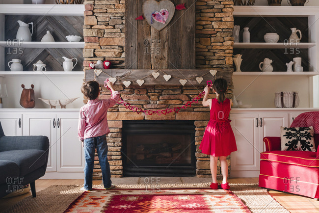 Young boy and sister decorating the fire place for St. Valentine's day