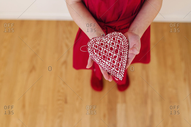 Little girl proudly showing ornamental heart she has made