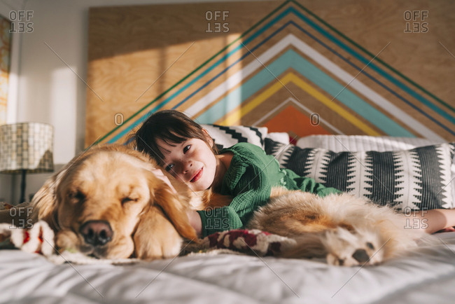 Young girl lovingly hugging pet Golden Retriever on the bed