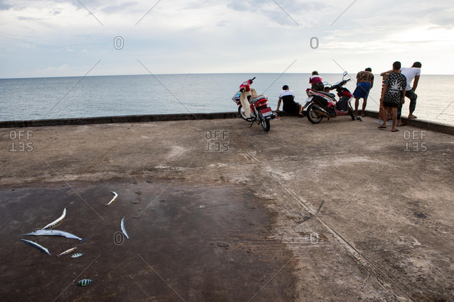 Koh Kood, Thailand - April 3, 2017: Men with scooters fishing on the island of Koh Kood, Thailand