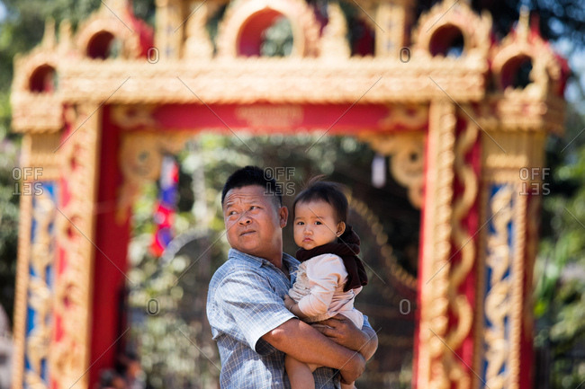 Vientiane, Laos - November 27, 2017: Man holding baby in a local village outside Vientiane, Laos