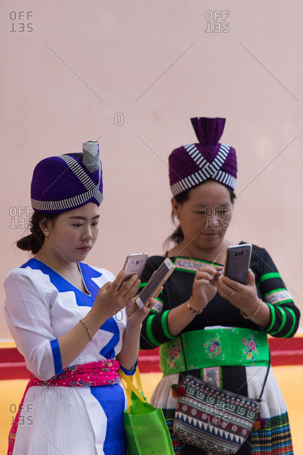 Vientiane, Laos - November 28, 2017: Women in local ceremonial clothing using cell phones in Nasala village, Laos