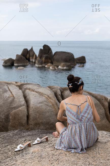 A woman sits at the Hin Ta and Hin Yai Rocks in Koh Samui, Thailand