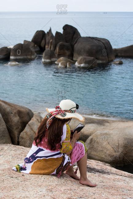 A tourist sits at the Hin Ta and Hin Yai Rocks in Koh Samui, Thailand