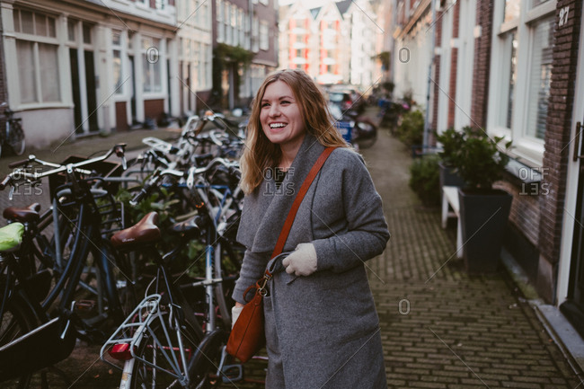 Woman walking and smiling on a cobblestone street in Amsterdam
