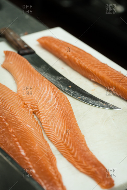 Salmon filets on cutting board with long knife