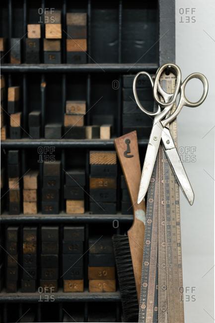 Letterpress tools, scissors, and rulers in printing workshop