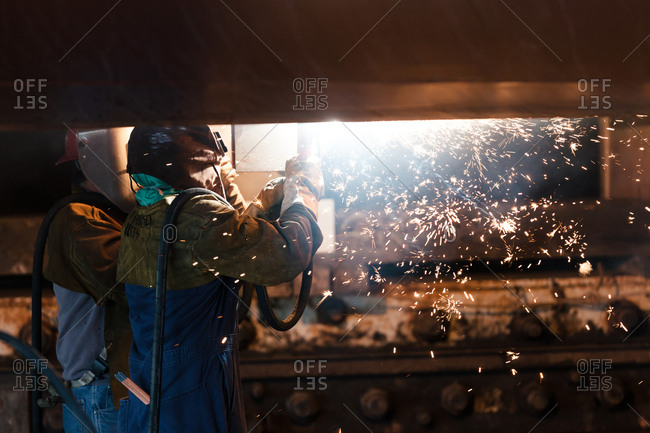 Workers welding a boat