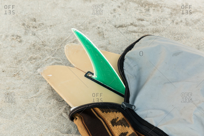Surfboard with a green fin on a beach