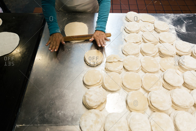 Stacks of uncooked tortillas and a rolling pin