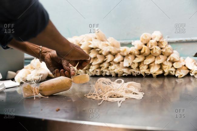 Chef tying sting onto tamales
