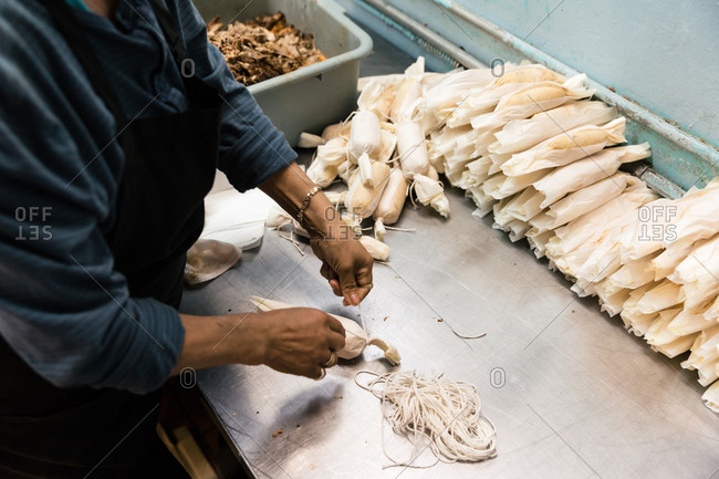 Overhead view of chef tying sting onto tamales