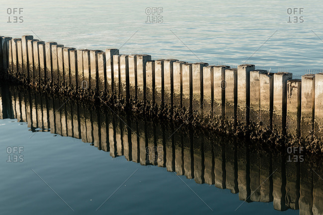 Cement structure reflecting in the San Diego Bay
