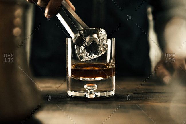 Man putting ice into a drink