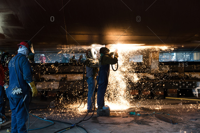 Workers welding at industrial boat launch