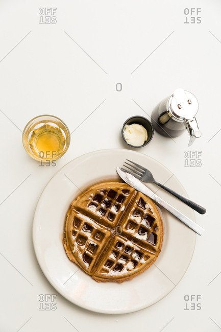 Belgian waffle served with butter, syrup, and a glass of whiskey