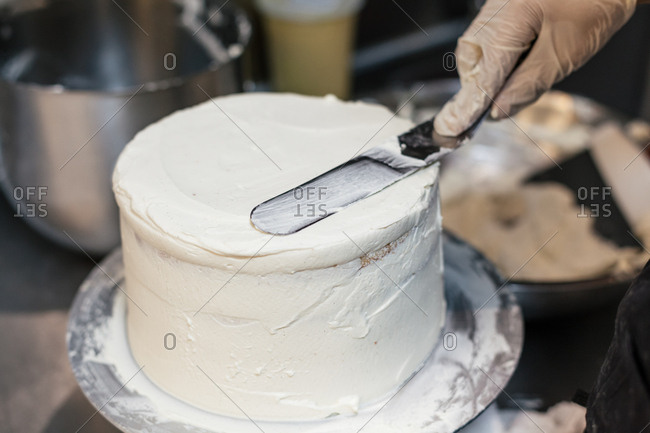 Person frosting a cake