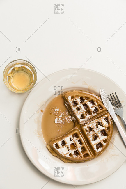Belgian waffle covered in maple served with whiskey