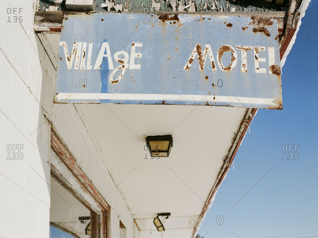 Weathered sign hanging from abandoned motel awning