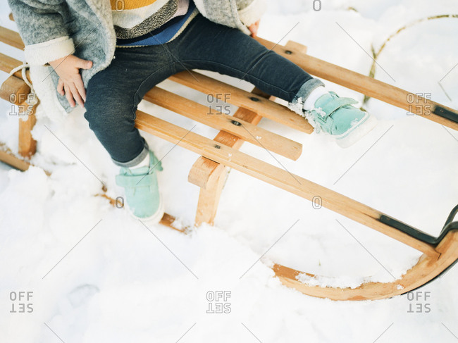 Toddler sitting on wooden sled in the snow
