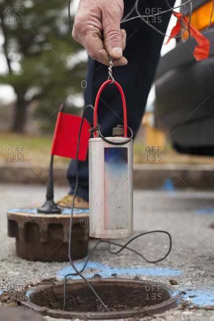 Water department technician lowering leak sensor