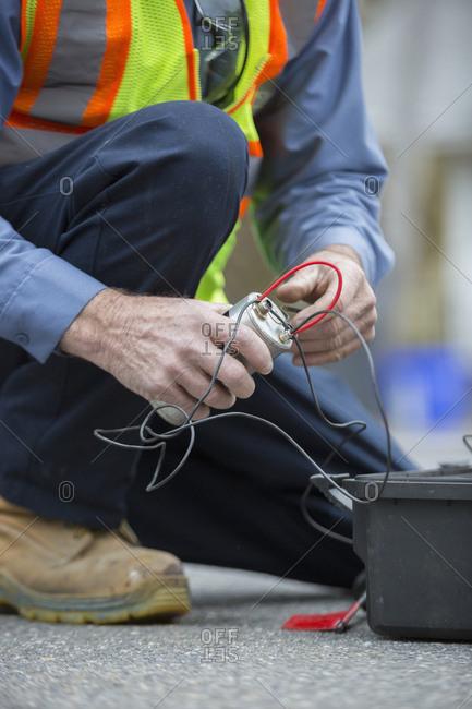 Water department technician using flow rate sensor