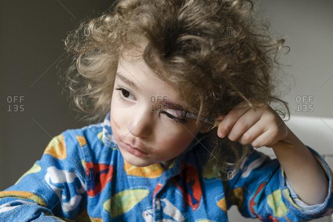 Young boy trying on eye shadow