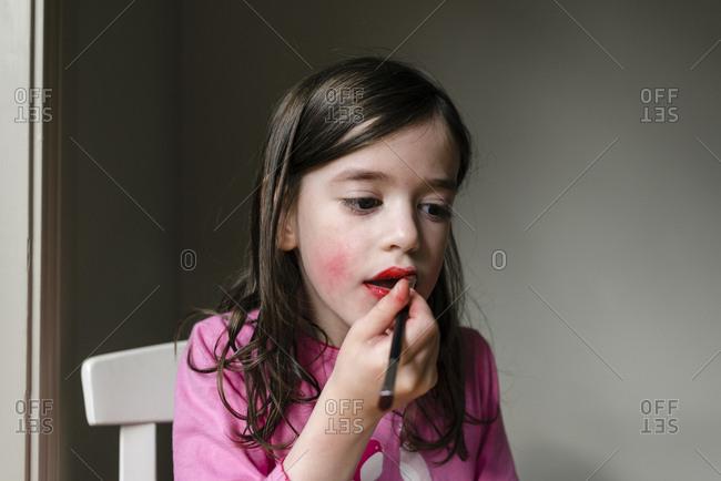Young girl applying lip stick