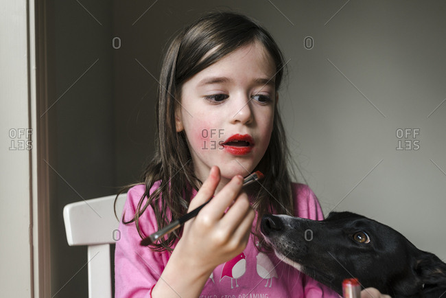 Young girl putting on lip stick as pet dog looks on