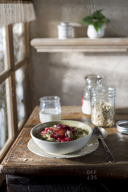Breakfast of muesli, milk, yogurt and fruit on a rustic table