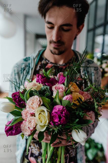 Man in flamingo t-shirt holding beautiful bouquet of roses and orchideas