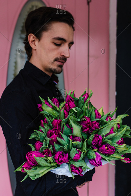 A man in black shirt holding big bouquet of lilac tulips