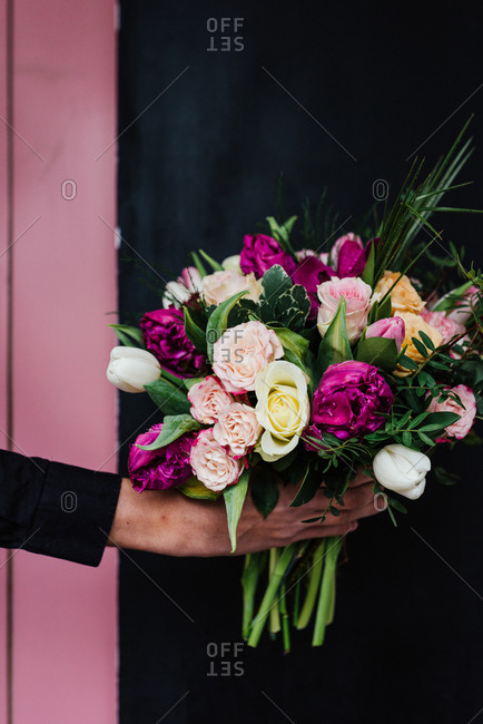 Man holding beautiful bouquet of fresh flowers like roses and orchideas
