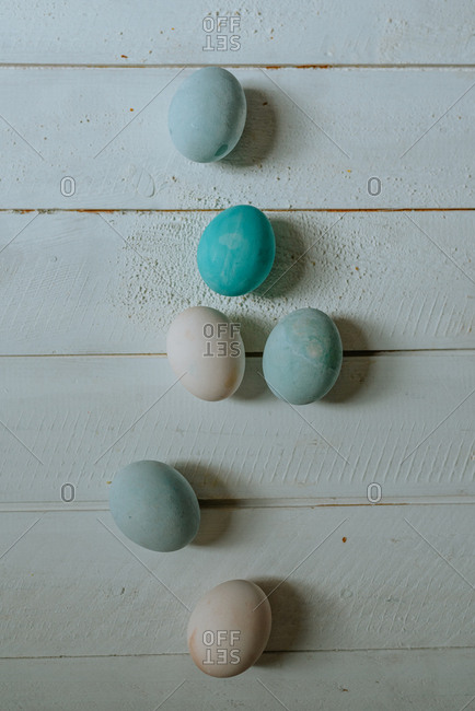 Pastel blue and white Easter eggs on a white wooden background