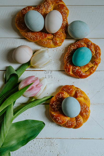 Pastel Easter eggs in braided pastry with tulips next to them