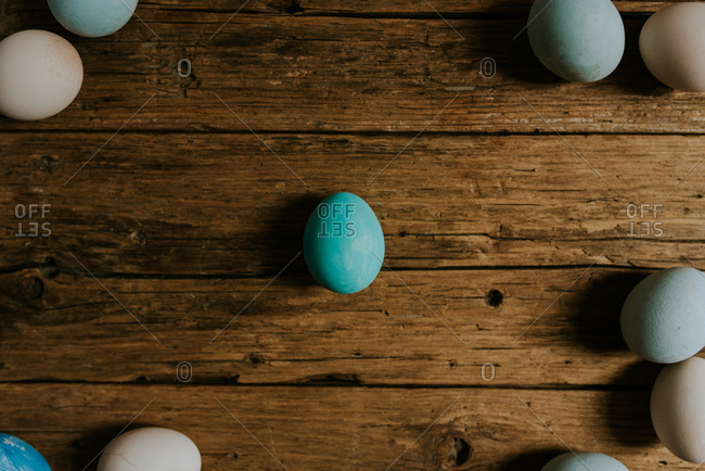 Pastel blue and white Easter eggs on a wooden background