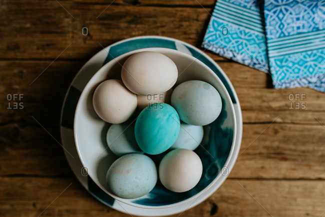 Pastel blue Easter eggs in a bowl placed on a wooden background
