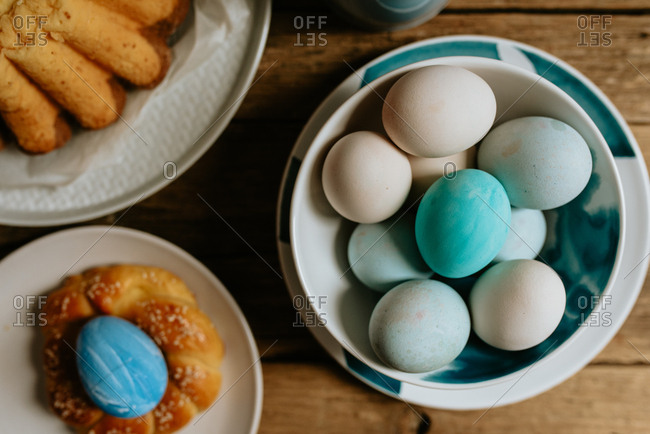 Pastel blue Easter eggs in a bowl placed on a wooden background next to the pastry