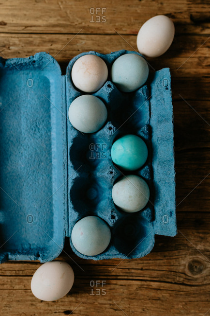 Pastel Easter eggs in a blue carton placed on a wooden background
