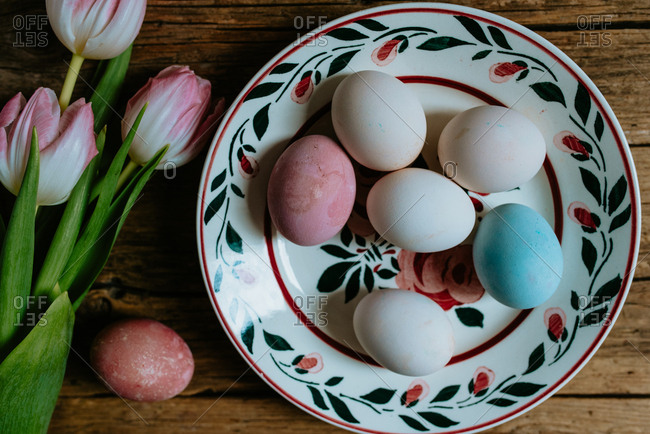 Pastel Easter eggs in decorative plate placed on a wooden background next to pink tulips