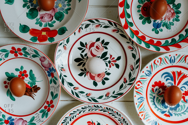 Eggs placed in beautiful plates painted with flowers and patterns placed on white background