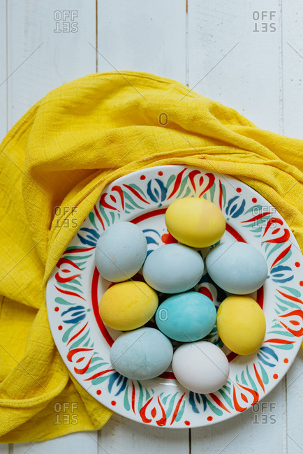 Yellow white and turquoise Easter eggs placed in matching color plate on a yellow cloth